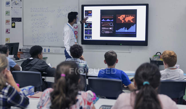 Male teacher leading lesson at touch screen television in classroom — Stock Photo