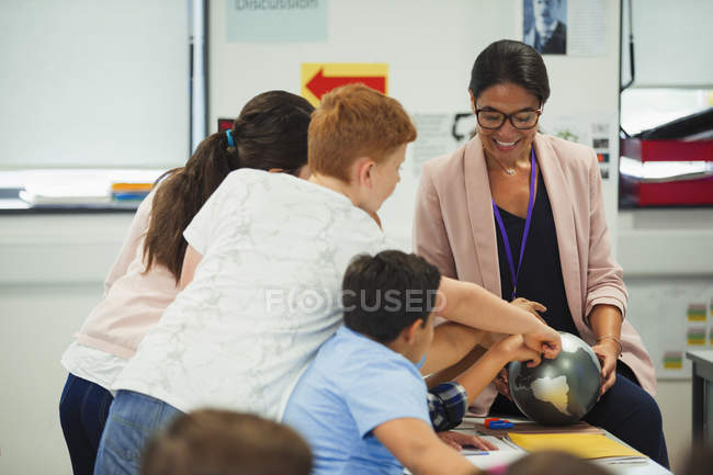 Junior high school students pointing at globe in geography teacher hands — Stock Photo