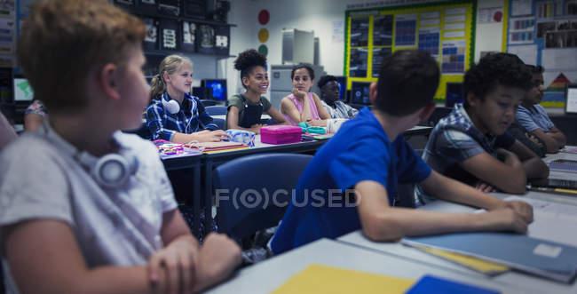 Studenti delle scuole medie alle scrivanie in classe — Foto stock