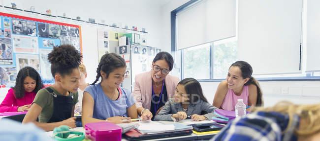 Insegnante femminile e studenti delle scuole medie alla scrivania in classe — Foto stock