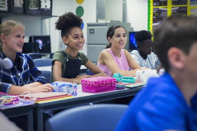 Sorridenti studenti delle scuole superiori alla scrivania in classe — Foto stock