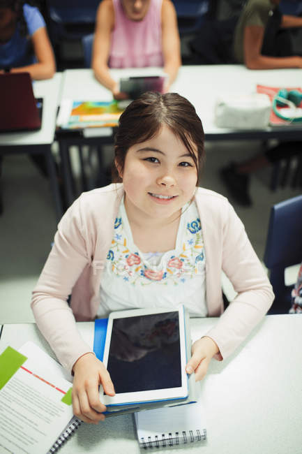 Portrait of smiling, confident junior high school student using digital tablet in classroom — Stock Photo