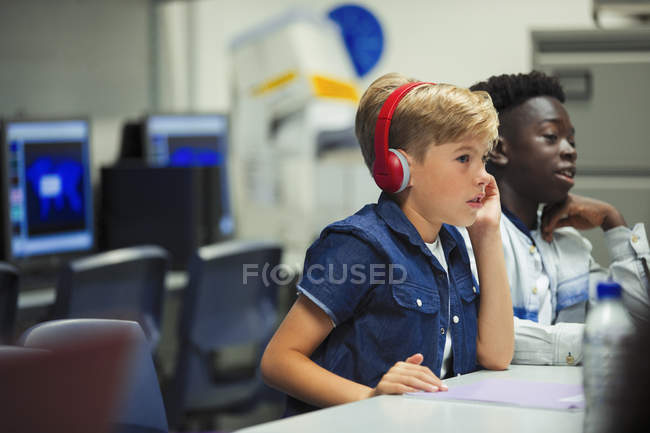 Focused junior high school boy with headphones in classroom — Stock Photo