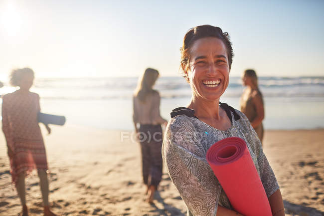 Portrait happy woman with yoga mat on sunny beach during yoga retreat — Stock Photo