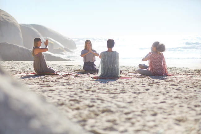 Gruppe meditiert im Kreis am sonnigen Strand während des Yoga-Retreats — Stockfoto