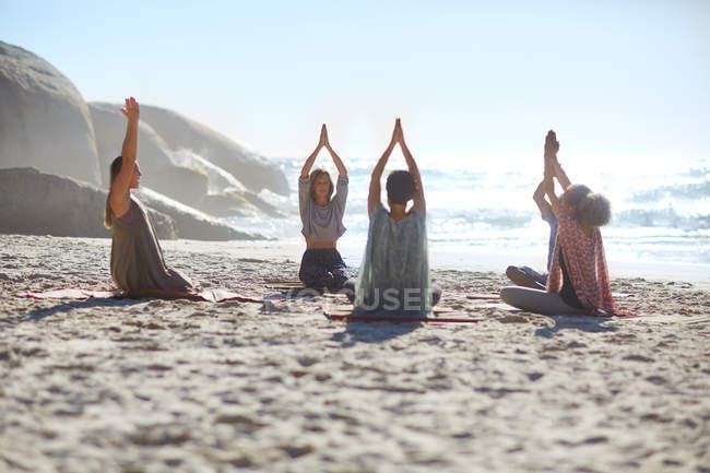 Povos sereno no círculo que meditando na praia ensolarada durante o recuo da ioga — Fotografia de Stock