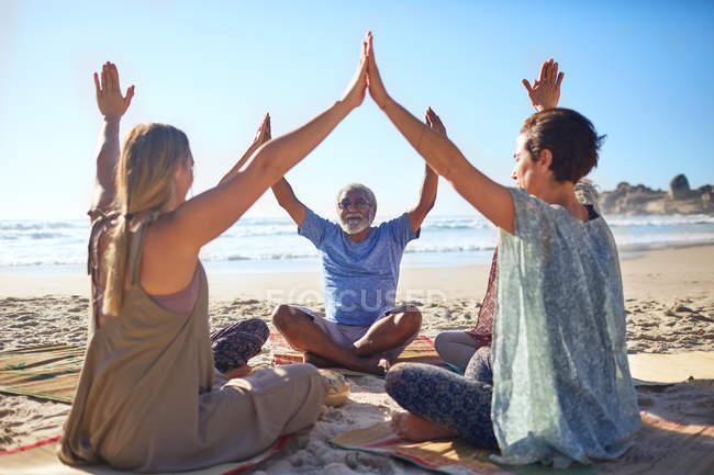 Группа, объединяя руки в круг на солнечном пляже во время йога отступление — стоковое фото