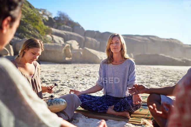 Heitere Frau meditiert während Yoga-Retreat im Kreis am sonnigen Strand — Stockfoto