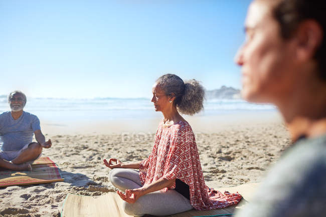 Serene senior woman meditating on sunny beach during yoga retreat — Stock Photo