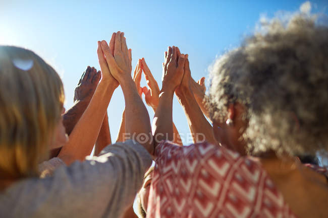 Group with hands clasped in circle during yoga retreat — Stock Photo