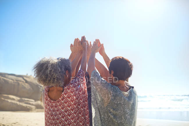 Frauen mit im Kreis erhobenen Armen am sonnigen Strand beim Yoga-Retreat — Stockfoto