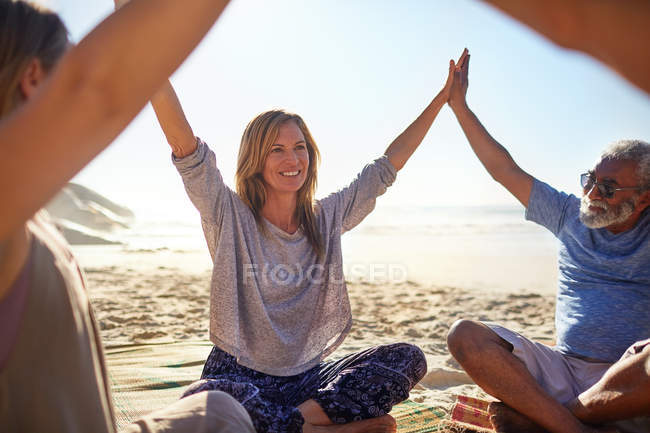 Happy friends joining hands in circle on sunny beach during yoga retreat — стоковое фото