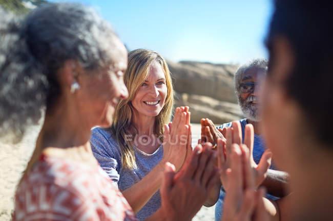 Freunde mit im Kreis geklammerten Händen am sonnigen Strand beim Yoga-Retreat — Stockfoto