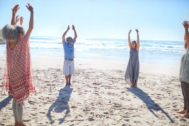 Group standing with arms raised in circle on sunny beach during yoga retreat — Stock Photo