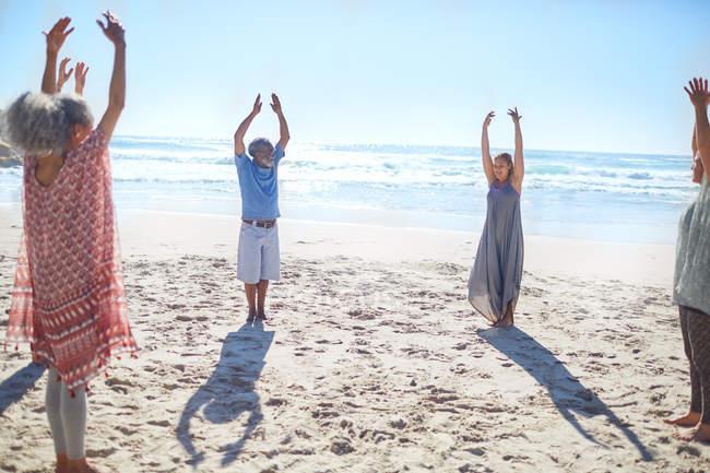 Группа стоялсов с поднятыми в кругна кругом на солнечном пляже во время йога отступление — стоковое фото