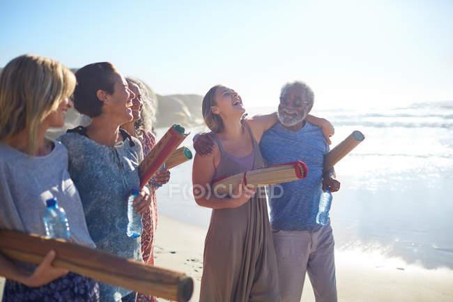 Heureux amis avec tapis de yoga collant sur la plage ensoleillée pendant la retraite de yoga — Photo de stock