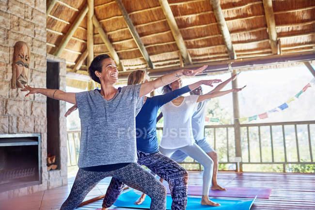 Glückliche Frau praktiziert Yoga-Kriegerin 2 posiert in Hütte während Yoga-Retreat — Stockfoto