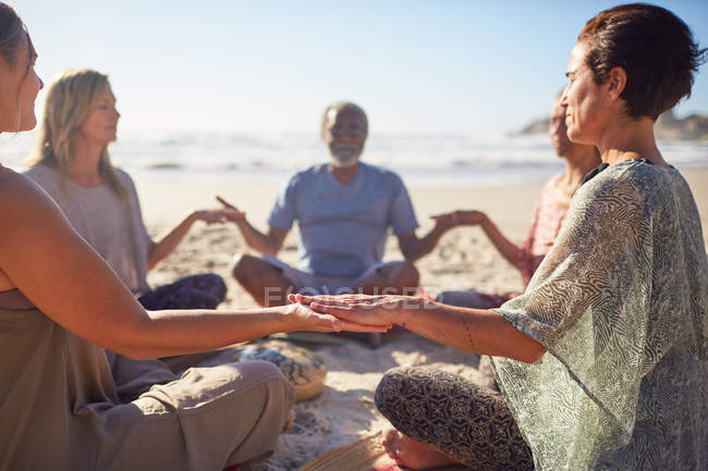 Serene people meditating in circle on sunny beach during yoga retreat — Stock Photo