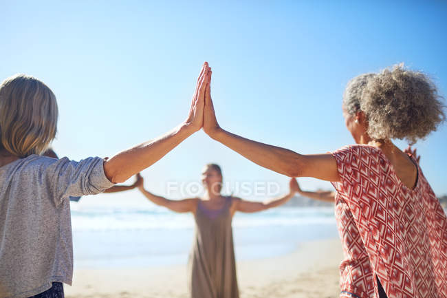 Women joining hands in circle on sunny beach during yoga retreat — Stock Photo