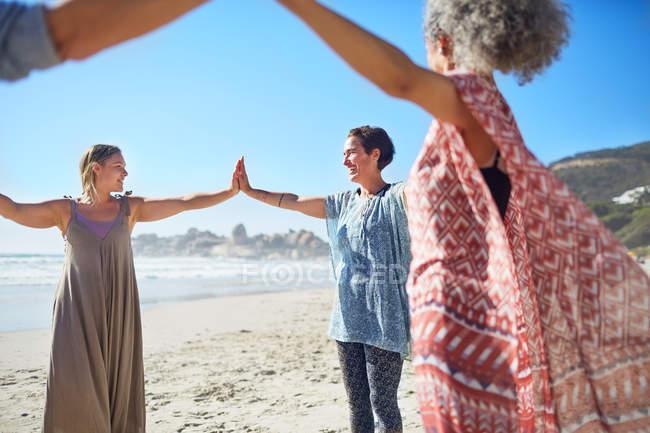 Женщины, соединяющие руки в круг на солнечном пляже во время йога отступление — стоковое фото
