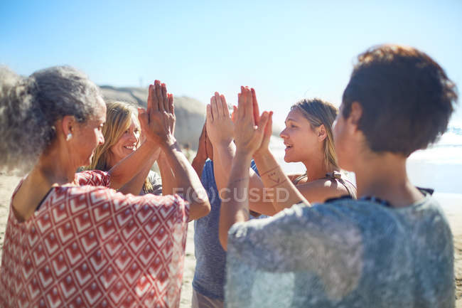 Group standing in circle with hands clasped on sunny beach during yoga retreat — Stock Photo
