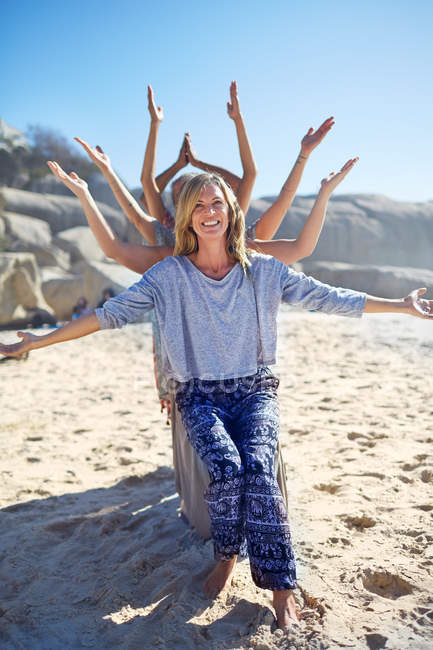 Portrait happy yoga class with arms outstretched behind woman on sunny beach during yoga retreat — Stock Photo