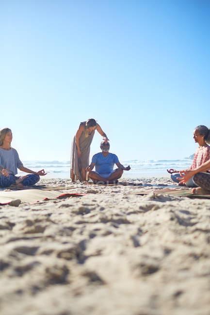 Ruhige Menschen meditieren am sonnigen Strand während des Yoga-Retreats — Stockfoto