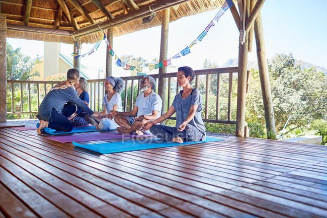 Heitere Menschen meditieren in Hütte während Yoga-Retreat — Stockfoto