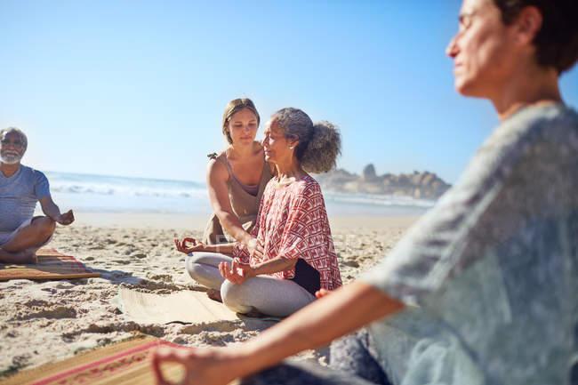 Gelassene Frauen meditieren am sonnigen Strand während des Yoga-Retreats — Stockfoto