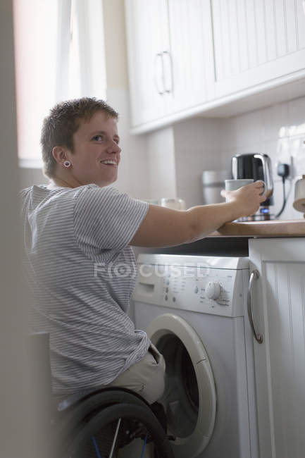 Young woman in wheelchair preparing tea in apartment kitchen — Stock Photo
