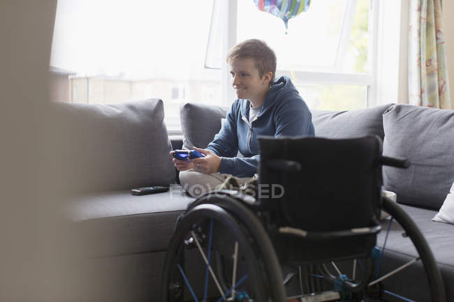 Young woman playing video game on sofa next to wheelchair — Stock Photo