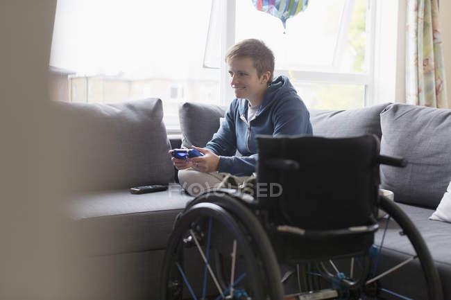 Jeune femme jouant jeu vidéo sur canapé à côté de fauteuil roulant — Photo de stock