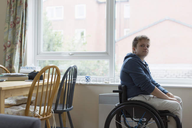 Portrait confident young woman sitting in wheelchair at window — Stock Photo