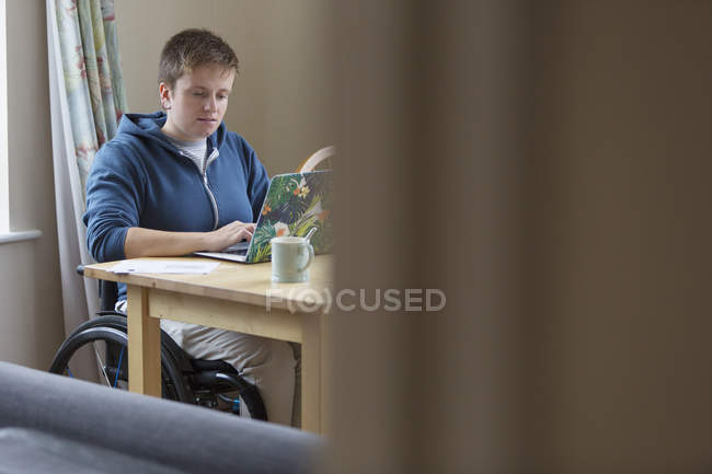 Young woman in wheelchair using laptop at dining table — Stock Photo