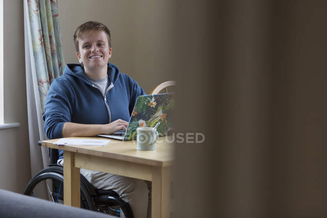 Portrait smiling, confident young woman in wheelchair at laptop — Stock Photo