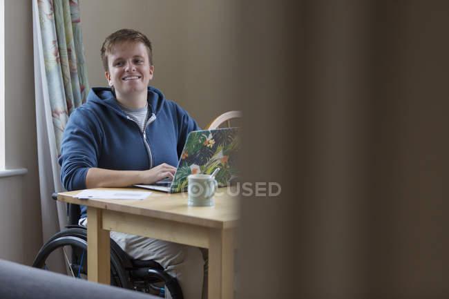 Porträt lächelnde, selbstbewusste junge Frau im Rollstuhl am Laptop — Stockfoto