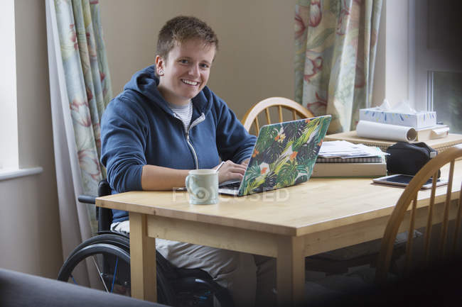 Portrait smiling, confident young woman in wheelchair using laptop at dining table — Stock Photo