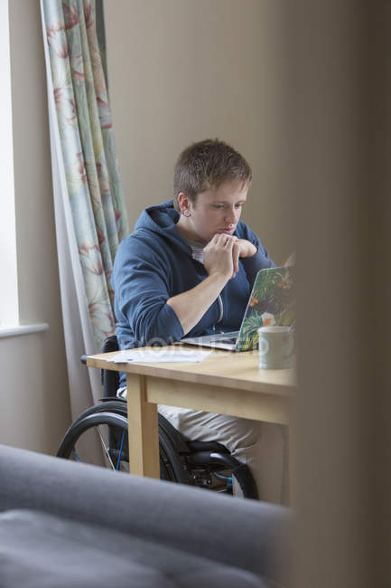 Focused young woman in wheelchair using laptop at dining table — Stock Photo