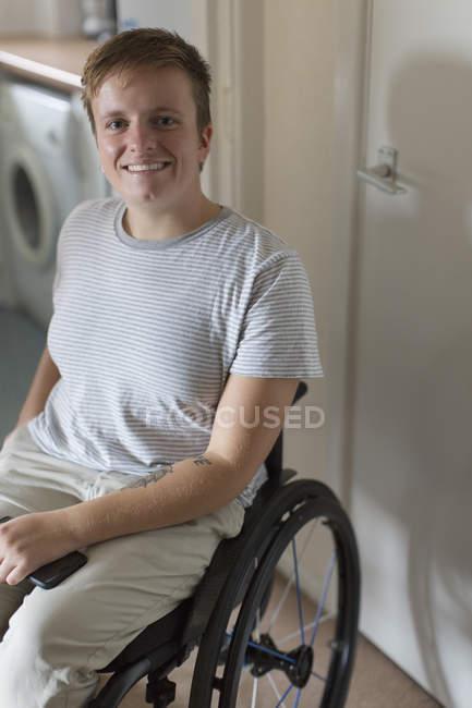 Portrait jeune femme souriante et confiante en fauteuil roulant à la maison — Photo de stock