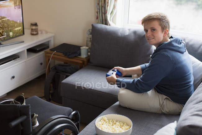 Portrait confident young woman playing video game on sofa next to wheelchair — Stock Photo
