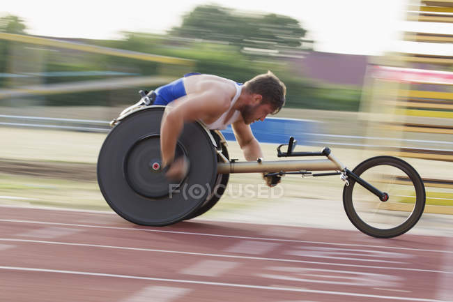 Determined young male paraplegic speeding on sports track in wheelchair race — Fotografia de Stock