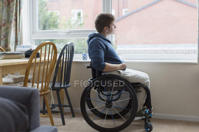 Jeune femme réfléchie en fauteuil roulant regardant par la fenêtre — Photo de stock