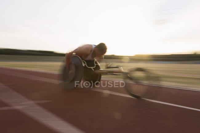 Решительный молодой парализованный спортсмен, мчащийся по спортивной трассе в гонке на инвалидных колясках — стоковое фото