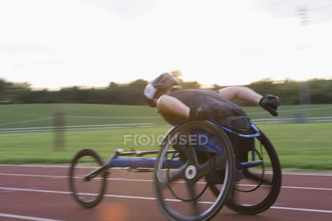 Atleta paraplégico acelerando ao longo da pista de esportes em corrida em cadeira de rodas — Fotografia de Stock
