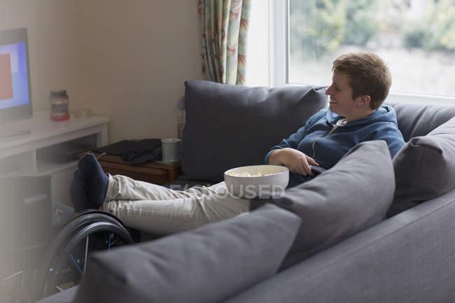 Jeune femme souriante se détendre sur le canapé, regarder la télévision et manger du pop-corn avec les pieds vers le haut sur fauteuil roulant — Photo de stock