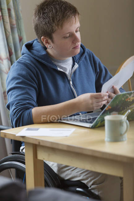 Young woman in wheelchair paying bills at laptop — Stockfoto