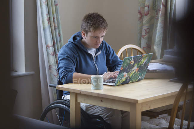 Цілеспрямований молоду жінку в інвалідному візку, використовуючи ноутбук обіднім столом — стокове фото