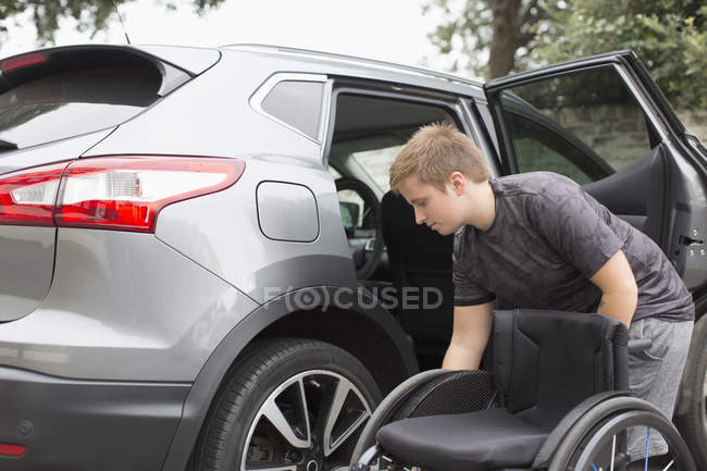 Young woman loading wheelchair into back seat of car — стокове фото