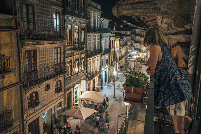 Woman standing on balcony, looking at ornate architecture, Porto, Portugal — стокове фото