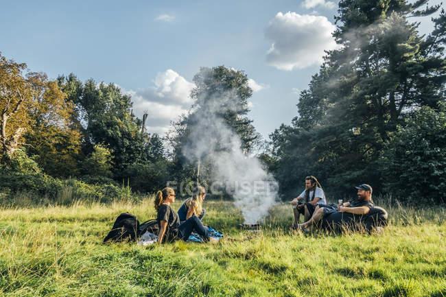 Amigos, acampar, relaxante ao redor da fogueira em campo remoto — Fotografia de Stock